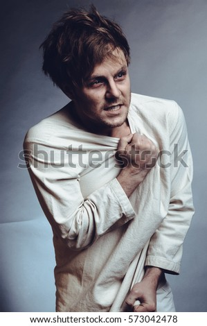 A mentally ill man in white clothes on a gray background