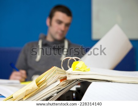 A messy dossier on top of a pile of paperwork in a cluttered office. Focus on the pages in the folder. - stock photo