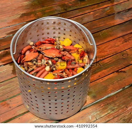 A metal basket of hot boiled crabs and crawfish with sausage, potatoes, corn on the cob, mushrooms and garlic, sitting on a wooden dock.