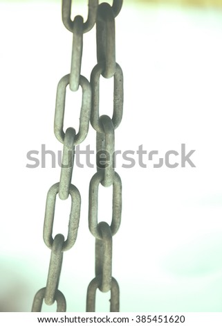 A metal chain against white snow. Image has a vintage effect applied. - stock photo
