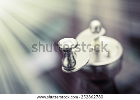 A metal coffee-mill handle on abstract background with rays of light beaming from the left - stock photo