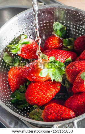 A metal colander resting in a kitchen sink, filled with fresh strawberries and being washed under a running tap. - stock photo