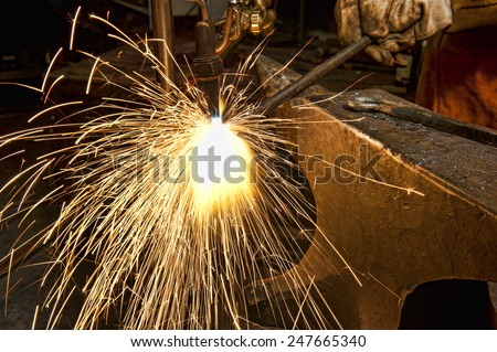 A metal fabricator utilizing a torch to heat up a piece of metal in order to shape it. - stock photo