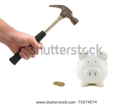 A metal hammer hammering a piggy bank isolated against a white background
