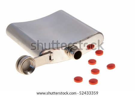 A metal hip flask laying down spilling a collection of red pills. - stock photo