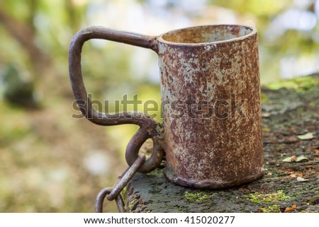 A metal mug for water with a chain near to a source.