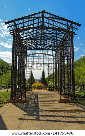 A metal pergola at the Randolph Street entrance to Maggie Daley Park in the Loop area of downtown Chicago is backlit against a bright blue sky - stock photo