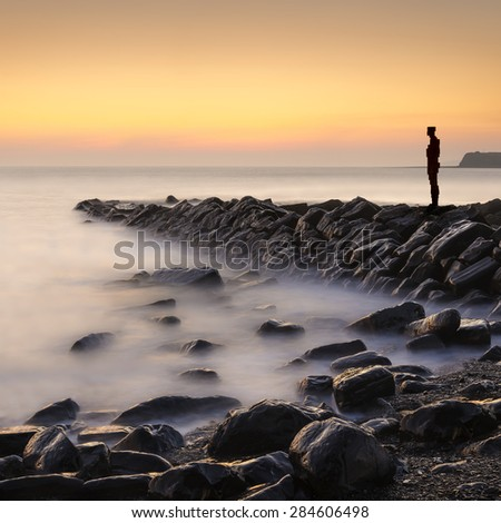 A metal sculpture on a stone jetty overlooks calm waters at Kimmeridge Bay, Dorset  - stock photo