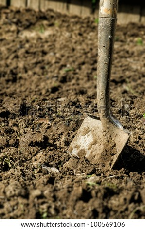 a metal shovel stuck in dirt