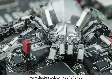 A metal spider standing on a printed circuit board - stock photo