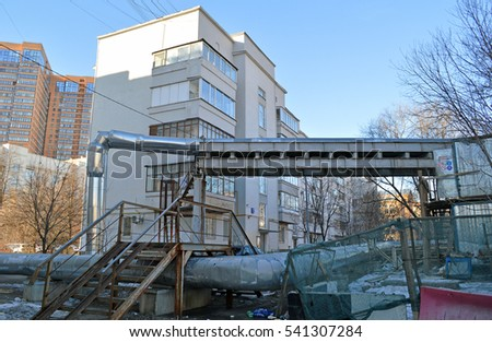 A metal walkway through the pipe heating plant on the background of an apartment house built in 1930 (Moscow)