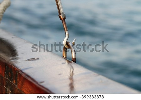 A metallic boat hook on wooden boat in the blue sea - stock photo