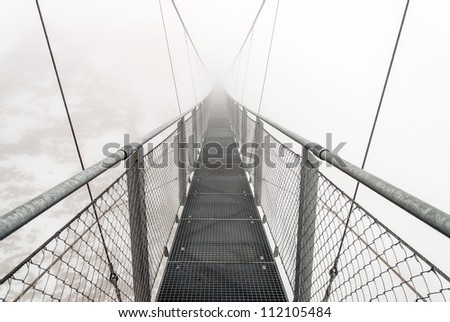 A metallic bridge for hikers in snowy Austrian Alps during a foggy day - stock photo