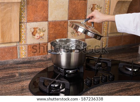 A metallic pan of boiling water on a modern gas cooker - stock photo