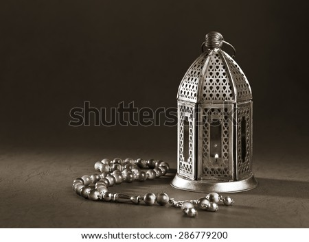 A metallic Ramadan lamp with Islamic rosary beads on black background. Monochromatic image. - stock photo