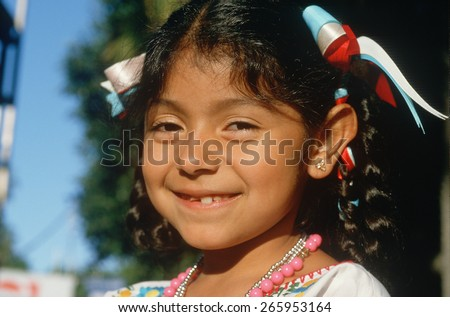 A Mexican-American girl with ribbons in her hair - stock photo