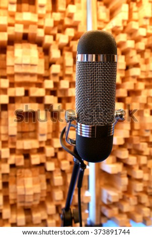 A microphone against a wooden sound proofing panel in a music recording studio. - stock photo