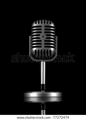 A microphone isolated against a black background - stock photo