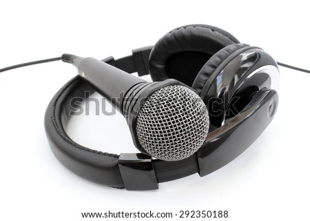 A microphone lying on black leather headphones