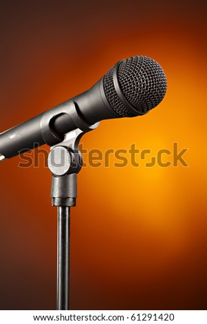 A microphone on a stand isolated against a spotlight gold background. - stock photo