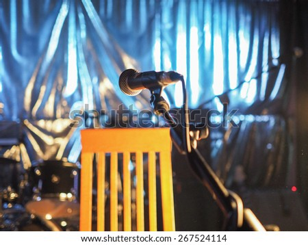A microphone on an empty stage before a concert - Selective focus on the mic with blurred background - stock photo