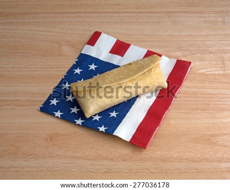 A microwaved chicken and cheese chimichanga on a flag motif napkin atop a wood table top. - stock photo
