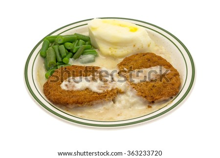 A microwaved fried chicken patties TV dinner with potatoes and green beans on a green striped plate isolated on a white background. - stock photo