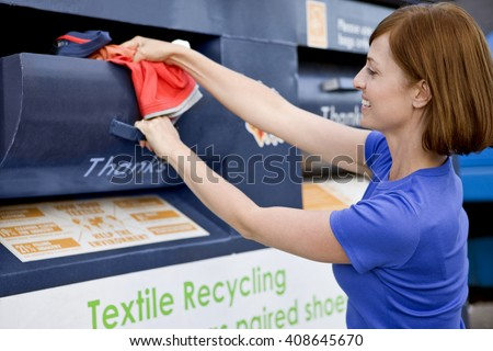 A mid-adult woman recycling clothes - stock photo