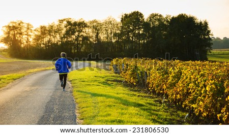A mid aged man running at sunset near the vineyard. Autumn in Loire Valley (Val de Loire, France) - stock photo
