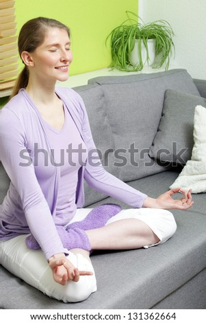 A mid aged woman relaxing with her eyes closed in a yoga pose