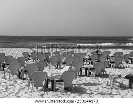 A mid-aged woman sitting alone at empty cafe on the beach (Tel Aviv, Israel). Loneliness concept. Aged photo. Black and white. - stock photo