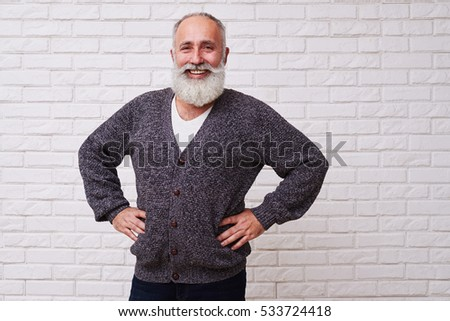 A mid shot of a merry grandpa wearing grey hand-knitted jacket. Man standing confidently with hands on his hips