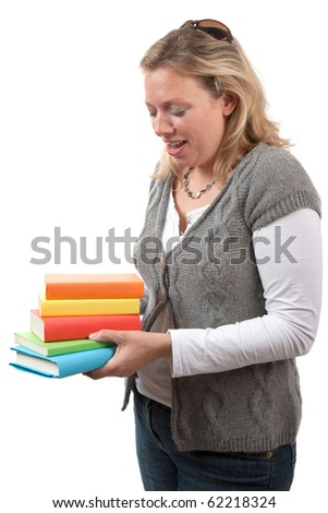 A mid thirties woman with long blonde hair holding a pile of colourful books.