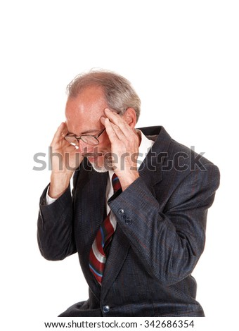 A  middle age man in a suit sitting with his hands on his head with headache