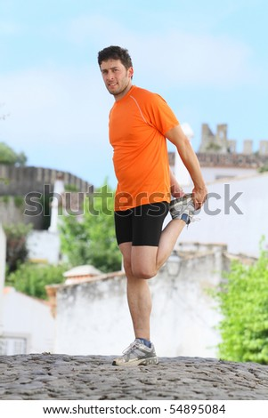 A middle age man making stretching movements before run - stock photo