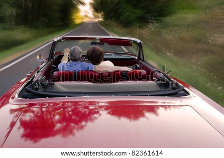A middle-aged couple snuggle together as they zoom down a county road in a classic red convertible, perhaps on a Sunday drive as they enjoy the experience and each others company. - stock photo