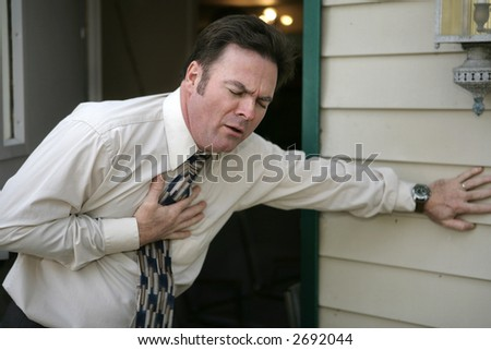 A middle aged man experiencing sudden chest pain. - stock photo