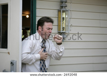 A middle aged man leaving a building and having a coughing fit.