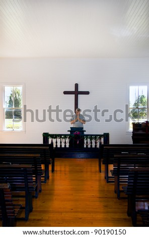 A middle aged man praying in a historic church at Christmas time. - stock photo