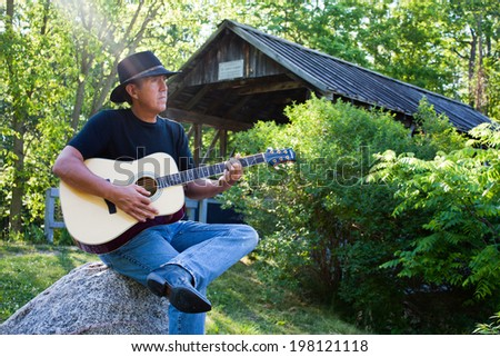 A middle aged man wearing a cowboy hat sits playing the guitar by the covered bridge in Petrolia Ontario Canada - stock photo