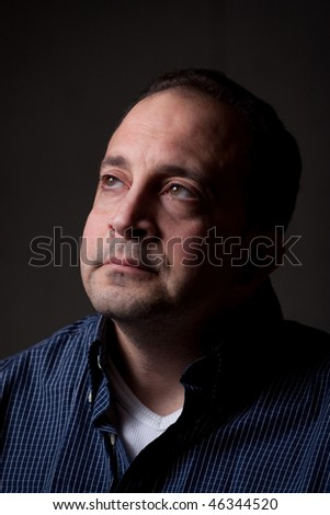 A middle aged man with a contemplative look on his face.  He could be worried or anxious about something.
