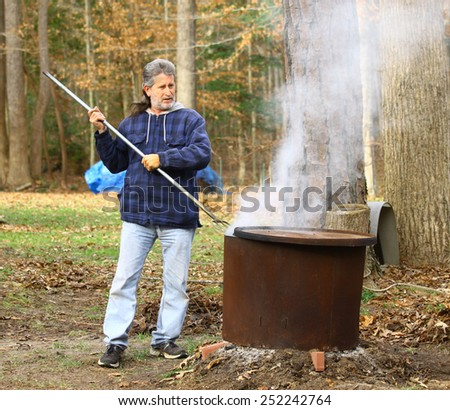 A middle aged man with a mullet working outside during the winter burning leaves and debris inside pf a fire ring around an old tree stump with a pitch fork
