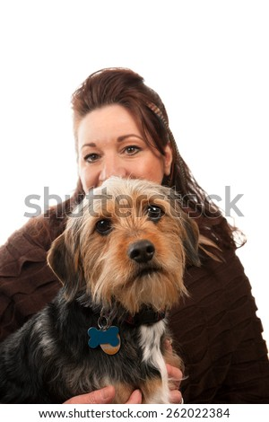 A middle aged woman isolated over white holding a cute mixed breed Borkie dog. - stock photo