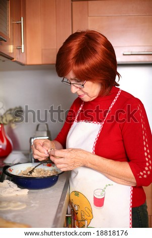 A middle aged woman stands in the kitchen cooking dinner
