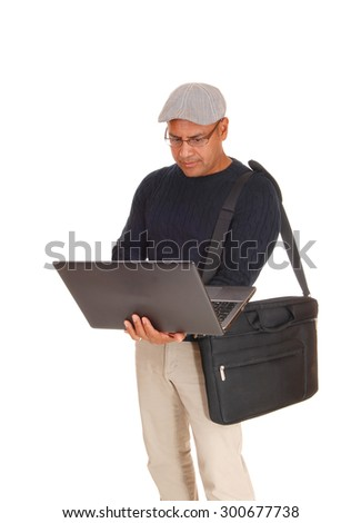 A middle ages Hispanic man standing isolated for white backgroundworking on his laptop with his bag over his shoulder. - stock photo