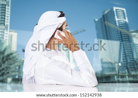 A Middle Eastern businessman talking on the phone and looking out the window in his office. - stock photo