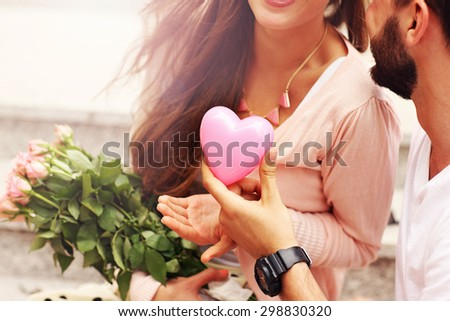A midsection of a romantic couple with flowers and heart - stock photo