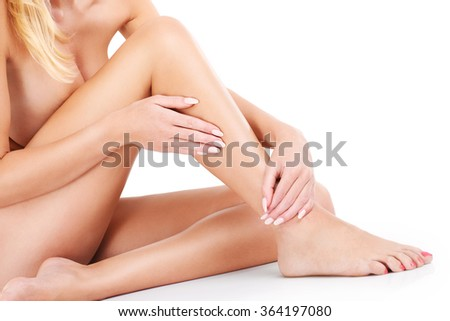 A midsection of naked woman sitting over white background - stock photo