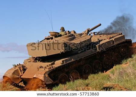 A military tank in action over rough terrain