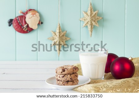 A milk glass and some chocolate chip cookies for Santa. On the background Santa Claus flies between gold stars on a turquoise wooden wainscot. Christmas vintage style. - stock photo
